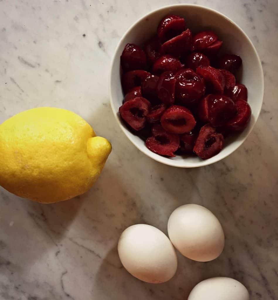 Ingrédients (citron, oeufs et cerises) pour le gateau aux cerises, amandes et citron