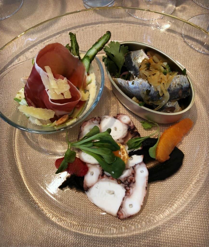 Fête de l'Érable : Une entrée en 4 temps avec salade d'asperges aux amandes rôties accompagnée d'une vinaigrette à l'érable doré, sucré-salé de sardines fraîches marinées, carpaccio de pieuvre pochée à l'eau d'érable, et pétoncle poêlé au beurre d'érable