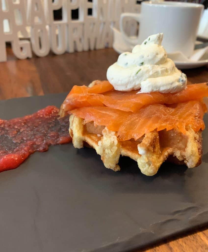 Servie en entrée, quart de gaufre surmontée de saumon fumé et d'une crème à l'estragon accompagné d'une compote de caneberges - Brunch au Méchant Boeuf- Happening Gourmand