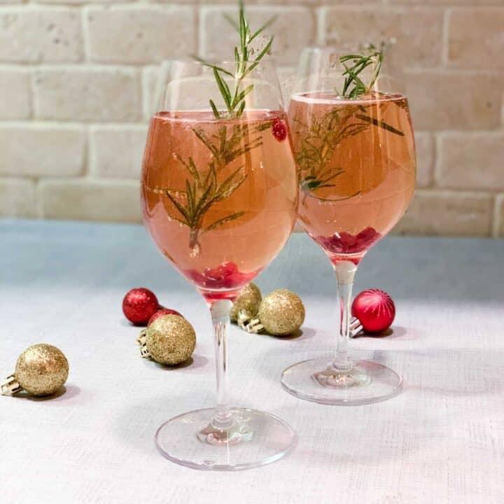 Cocktail festif avec canneberges, prosecco, st-germain et romarin