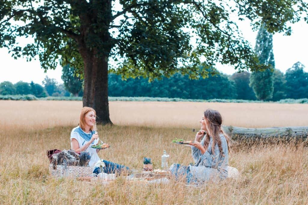 Deux amies qui font un pique-nique dans un parc l'été