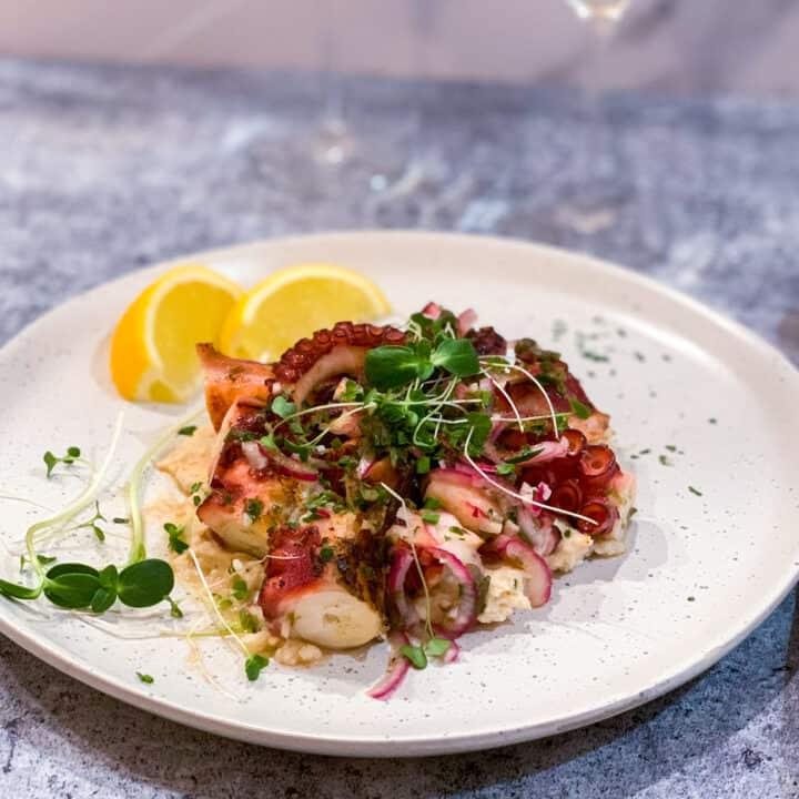 Salade de pieuvre grillée servie sur lit de purée de haricots blancs