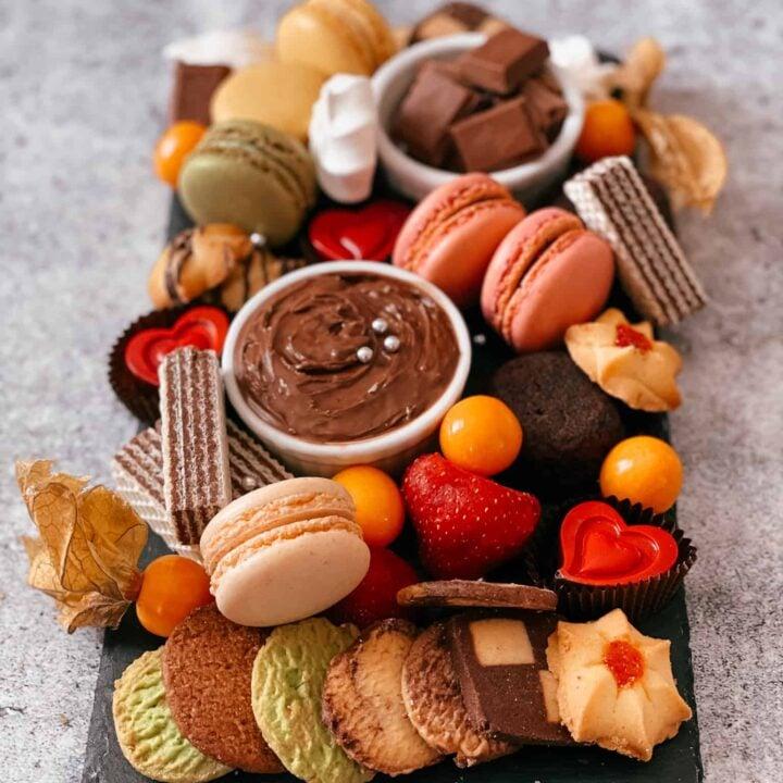Planche de desserts avec Nutella, biscuits, macarons, chocolat, gaufrettes et petits fruits