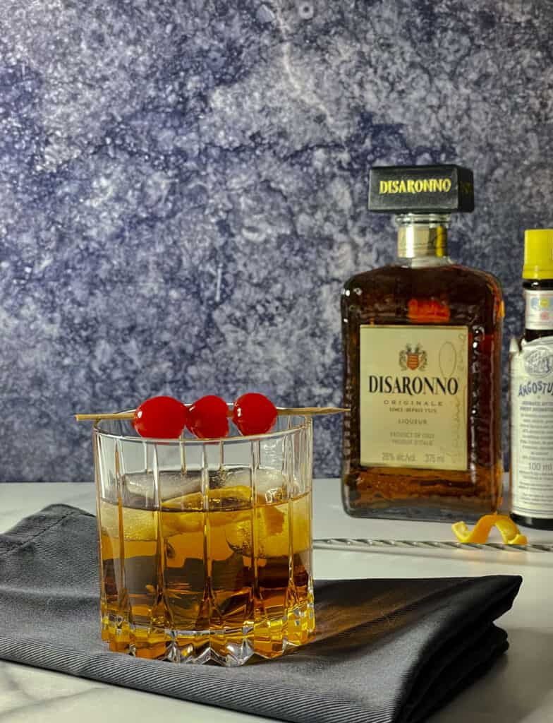 Old fashioned glass with a bottle of Disaronno and Angostura.