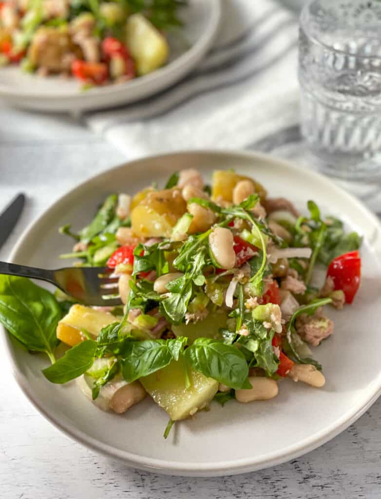 Plate of Sicilian style tuna salad with potatoes and white beans with a fork